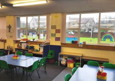 the classroom has yellow walls, blue tables and green plastic chairs, the room appears dark although there are a lot of windows.