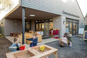 children are playing in the sand box in the outside learning area