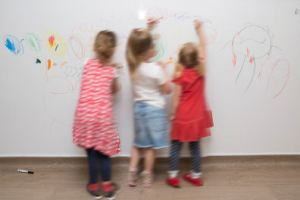 children using the whiteboard wall to draw on