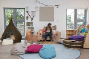 a cozy area of the room where a member of staff reads to two children on the cuddle sofa
