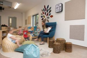 a library corner where a member of staff reads to two children from an armchair, the children are sitting in front on wicker chairs