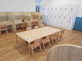 a large table with chairs in the centre of the room and individual work stations around the edge