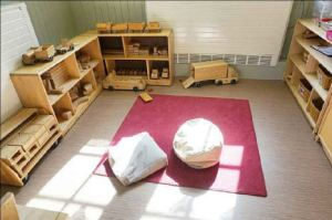 Block play and construction area, there is a rug and some bean bags to play and sit on