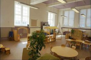 the classroom is laid out in well defined zones, a round table, a home area, a cozy corner