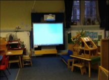 a Smart Board on the wall, in front of it is a small bench, chairs and tables