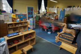 the classroom with a table and chairs, rocking horse and shelving used to break up the space