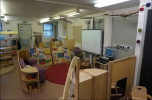 a teaching area with a smart board, rug and sofa makes it look cozy