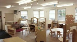 the classroom is bright and neutral with wooden furnishings