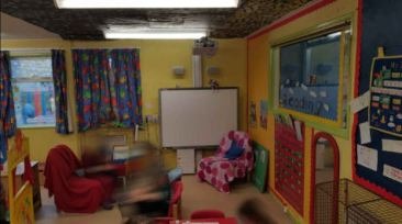 A comfy corner next to the smart board, the ceiling has black paper on it, the room looks dark