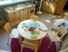 a home corner with wooden chairs and table, kitchen and kitchenware