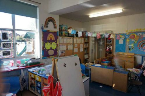 an art easel and storage, lots of colourful displayed work