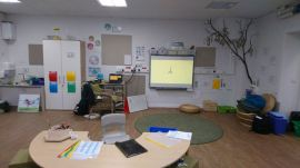 the teacher has a comfy wicker chair beside the whiteboard, the children sit on a rug