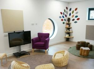 The teaching space in front of the interactive screen, a purple armchair for the teacher and wicker baskets on a rug for the children to sit at