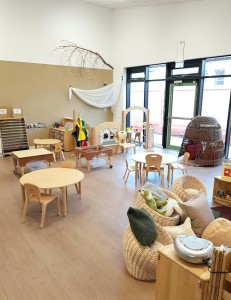 the classroom with large windows from the floor, wicker basket chairs and cushions. three round tables with chairs, a wicker nook and sand and water play units.