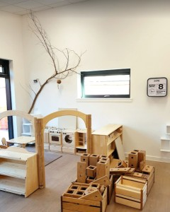 a home corner with play kitchen is accessed through a little archway, outside of the partitioned area are lots of blocks for construction. A branch hangs on the wall