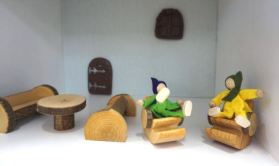 Wooden doll house pieces set up with two benches and a table and two people sitting on chairs