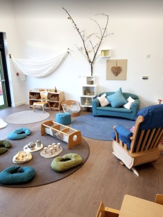 the cozy seating area looks like a living room with an adult rocking chair, sofa, floor cushions and three circular rugs