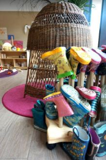 A welly rack in front of a wicker nook for a child to hide in