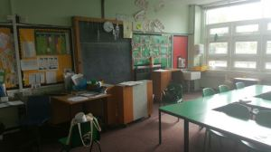 the teaching wall has a blackboard and teachers desk, the room is bright with natural daylight but the furniture and carpet darkens the room