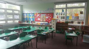 the classroom decoration appears cluttered with paper displayed on the walls and on the windows which makes the room darker