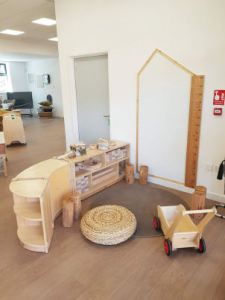 a giant ruler is on the wall beside a house shaped white board, a wicker seat pad is on a rug on the floor beside the block play storage that is low down for children to access