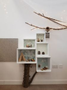 nature inspired decoration, this shelving unit has a tree trunk from the floor to the base of the unit, a branch with fairy lights is hanging on the wall above