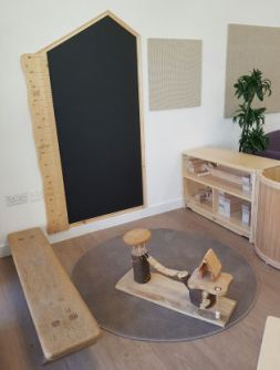A giant wooden ruler is on the wall beside a house shaped blackboard for children to write on. a bench is beside a dolls house which is sitting on a circular rug