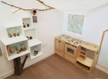 a home corner has a play kitchen and Nature inspired decoration