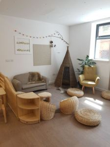 A cosy corner with cuddle sofa, an armchair and a wicker teepee in the corner. wicker basket seats and floor pads are scattered on the floor around a circular rug