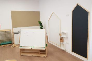 a creative area with two house shaped drawing boards on the wall, an art station and a drying rack