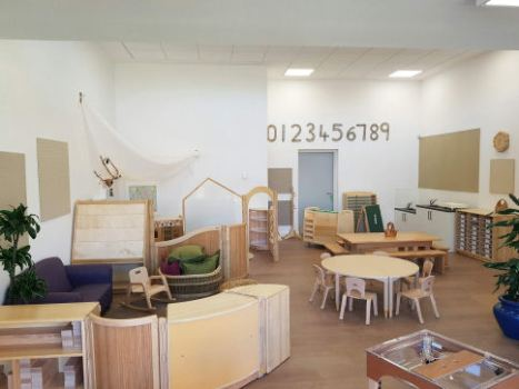 in the classroom there are water and sand play units, areas are partitioned off using low down shelving units, there is a circular table and chairs and numbers on the wall