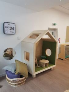 A house shaped nook with a rocking chair and small table inside enough for two children to sit in