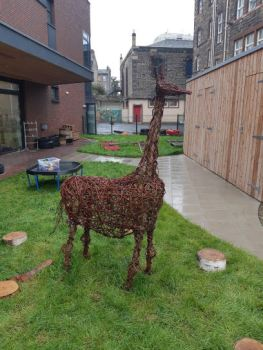 outside in the garden are little log seats and a sculpture of a giraffe