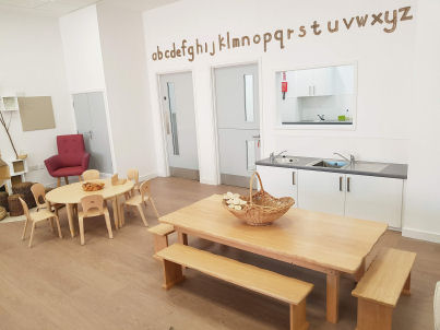 Dining area with kitchen hatch, sinks and table with benches
