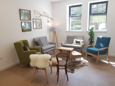 an adult area that looks like a living room with a mixture of different armchairs and wooden chairs in a circle, coffee table and a rug in the centre and a lamp in the corner