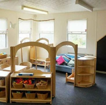 A cozy corner, on the wall there is a blackboard in the shape of a house for children to use, a wooden play kitchen and a sofa