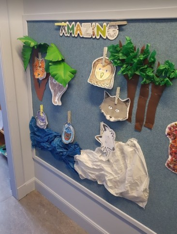 textured blue pinboard with a display of children's work, there are trees and animals