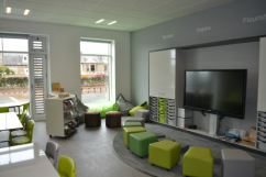 Soft seating around the teaching wall, upholstered stools are different shades of green and grey and can be separate or pushed together to make a large bench