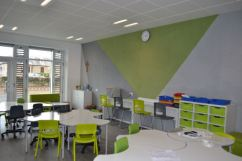 Cloud shaped tables fit together or can be separated, a pinboard in grey and green fill the whole wall