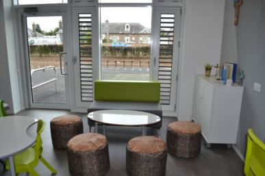 four stools that look like cut logs surround a coffee table, a sofa is by the window