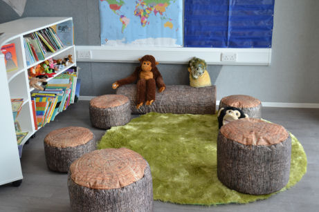 five stools that look like cut logs and one long one lying on the floor surround a furry rug creating a homely reading corner