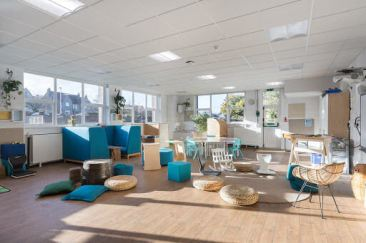 the room is bright and airy, there are plants hanging on the walls. the colour scheme is mostly natural wood with a few upholstered furnishings in blue.