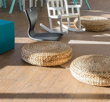 On the floor of the classroom surrounding a circular rug are three wicker seat pads, an upholstered blue cube seat, a plastic floor seat which has a high back support and no legs and rocks and a white rocking chair.