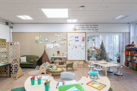 the ferry glen classroom has a half circle teaching table, a divider that has holes in it to see through, a cozy corner and a rectangular teaching table and inspirational quote on the wall