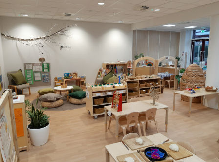 the classroom with lots of natural decoration, wooden tables, chairs and storage units, plants are placed around the room, baskets, floor pads and a hideaway nook are made from wicker, there is a branch with fairy lights hanging on the wall