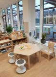 large windows line the classroom wall so the children can see out to the outdoor area, a hexagonal table and wobble stools are set up for an activity