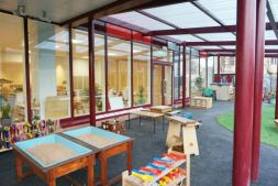 the outdoor space underneath a canopy where there is sand play units and a workbench, there is a welly rack. The space has been designed like an outdoor classroom