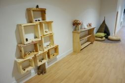 wooden box shelving on the wall is shaped like a tree with a trunk at the bottom going down to the floor. a wooden bookshelf sits next to a cozy reading area with a wicker teepee and seat pads resting on a circular rug