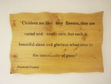 "a sign saying ""children are like tiny flowers, they are varied and need care, but each is beautiful alone and glorious when seen in the community of peers"""