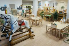 in a classroom there a two traditional wooden rocking horses, three wooden tables, sand and water plat units, a wicker teepee and wicker baskets in storage shelving that is low enough for the children to reach